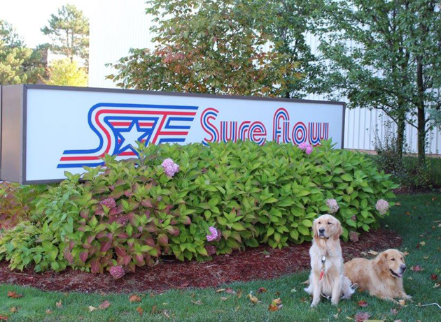 Odus and Acer in front of the Sure Flow sign